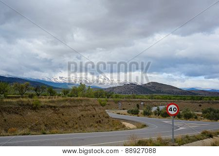 Zigzag road in Spain with snow mountains