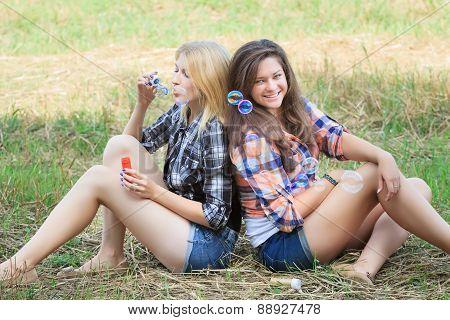 Blonde girl blowing multicolor soap bubbles near her brunette friend