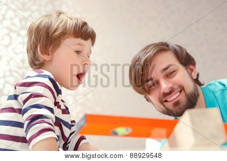 Father and son play with a building kit