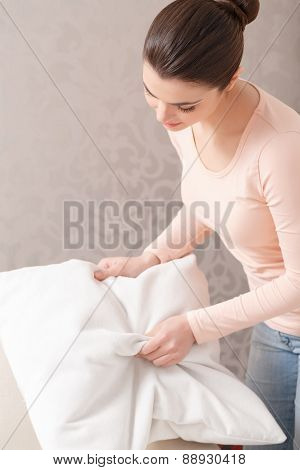 Woman punching pillow into shape