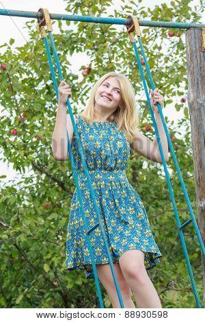 Blonde student girl in azure blue silk sundress standing on handmade swing