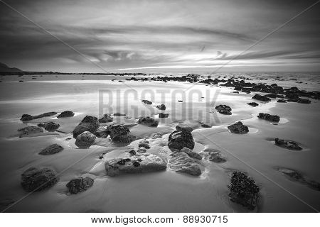 Sunrise Dawn Landscape On Rocky Sandy Beach With Vibrant Sky And Clouds In Monochrome