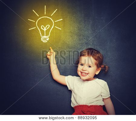 Concept, The Idea Of A Happy Little Girl With A Bulb At The Blackboard