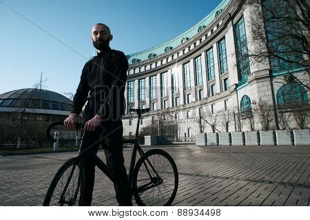 bald bearded guy with black fix against building