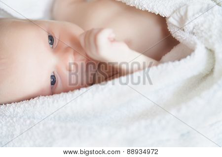newborn tiny baby lying on the bed side view