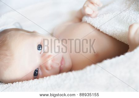 newborn tiny baby lying on the bed close-up