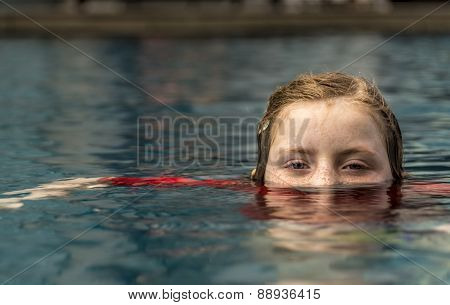 Young Girl Swimming In Pool With Face Half Submerged Looking At Camera