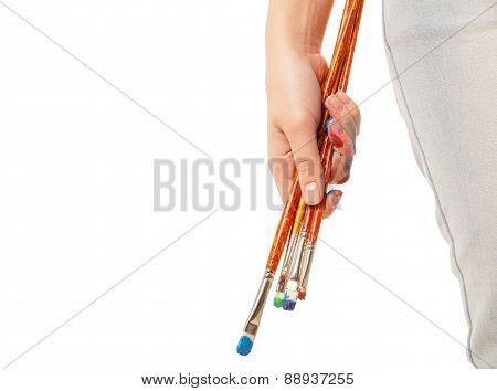 Hand holding brushes isolated on white