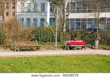 person sleeping in a sleeping bag on a bench. Poverty and loneliness in the city (France)