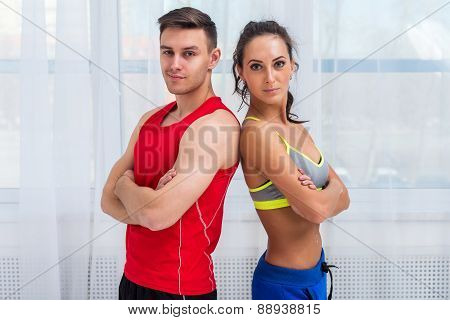 athletic sporty couple friends woman and man trainers or coach client in sport hall gym standing arm