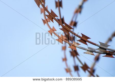 Rusty Barbed Tape Cutter Against Blue Sky, Close Up