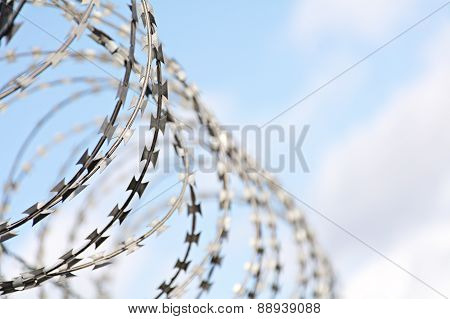 Barbed Tape Cutter Against Blue Sky With Clouds