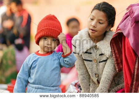KATHMANDU,NEPAL,NOVEMBER 04,2010: A little boy wearing a red woolly hat is posing at the street market in the historical Patan Durbar square in Kathmandu, Nepal