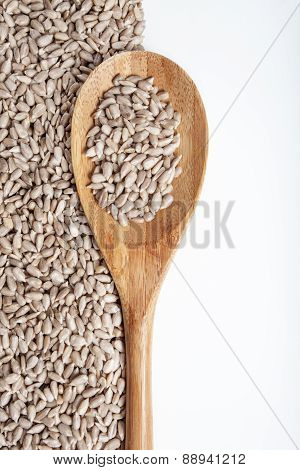 Sunflower seeds and spoon on a white background.