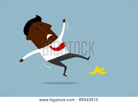 African american businessman slipping on a banana peel