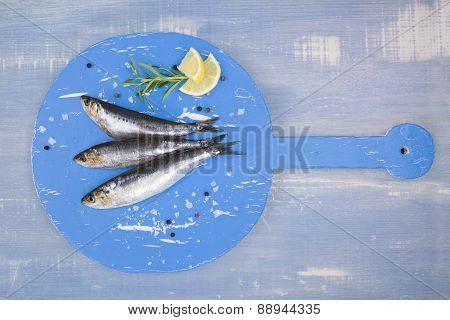 Fresh Anchovy Fish On Blue Wooden Kitchen Board.