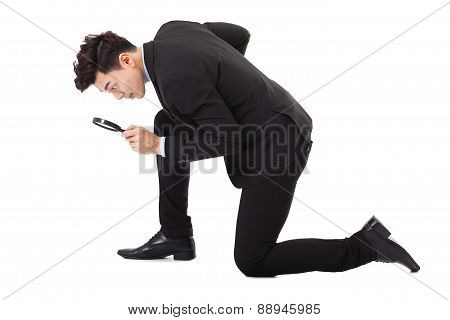 Businessman Looking Through Magnifying Glass For Searching