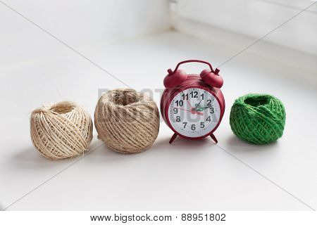 Three Skeins Of Thread And Red Clock In A Row