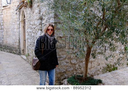 Beautiful Girl With Brown Hair Near Olive Tree On The Mediterranean Style Court And Old Stone Wall B