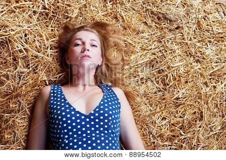 Closeup Of Beautiful Girl With Long Blond Hair Lying On Hay And Looking At Camera
