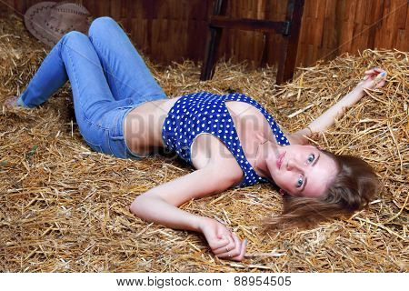 Beautiful Smiling Girl With Blond Hair In Jeans Lying On Hay And Looking At Camera