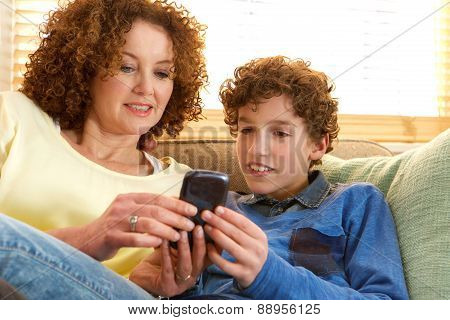 Happy Mother And Son Sitting On Sofa At Home