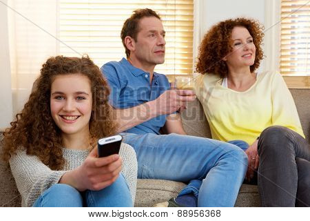 Happy Girl Holding Television Remote Control With Parents In Background