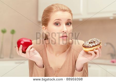 Woman holding apple and a donut