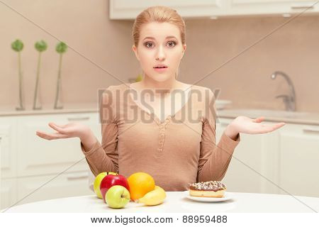 Woman making choice between fruit and donut
