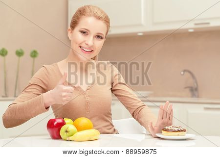 Smiling lady sits between fruit and dessert