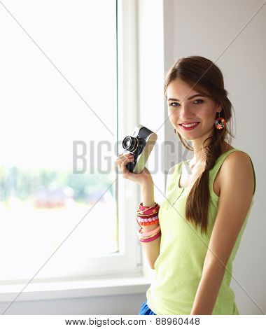 Beautiful young woman with camera standing near dark wall