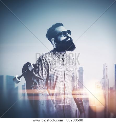 Beard Man With Longboard And Sunglasses On Blurred City Background