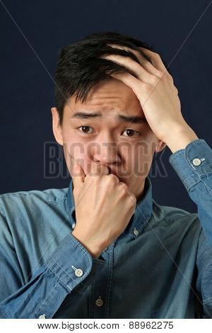 Disappointed young Asian man looking sideways