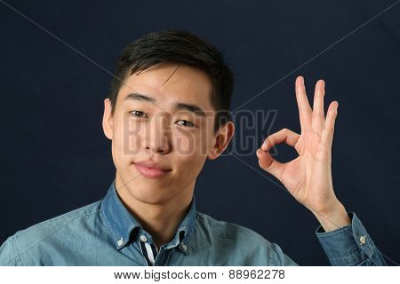 Pleased young Asian man giving okay sign
