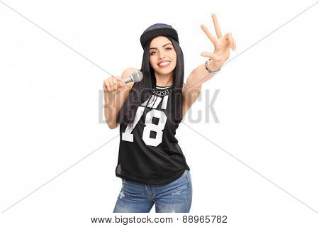 Young female hip-hop artist singing on a microphone and making a hand sign isolated on white background