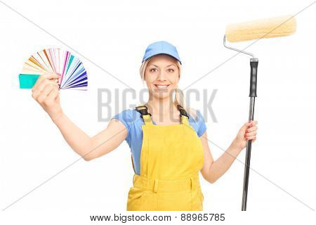 Blond female decorator holding a paint roller and a color palette guide isolated on white background