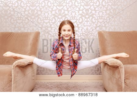 Little flexible girl splitting legs apart
