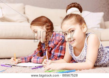 Two little girls lying on carpet