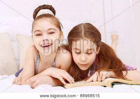 Pair of little girls reading book