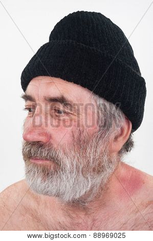 Portrait of elderly man with a beard and black hat