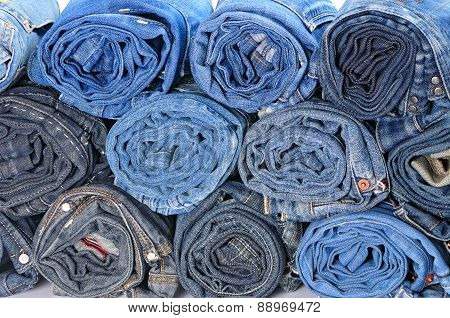 Stack Of Rolled Colored Jeans. Front View