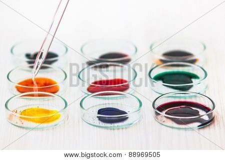 Various colored chemicals in lab dish and pip pipette