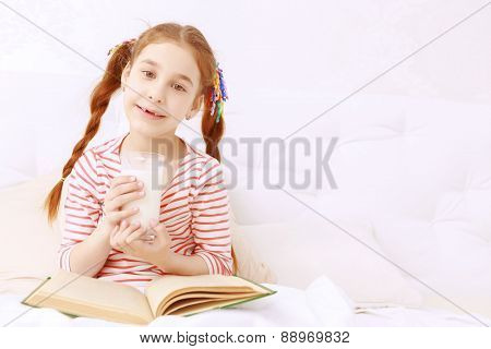 Read-haired girl drinking milk and reading