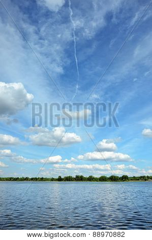 Summer landscape with river and cloudy sky