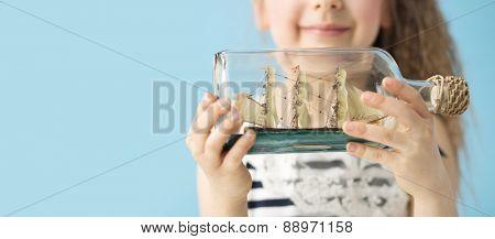 Little girl holding ship in a bottle