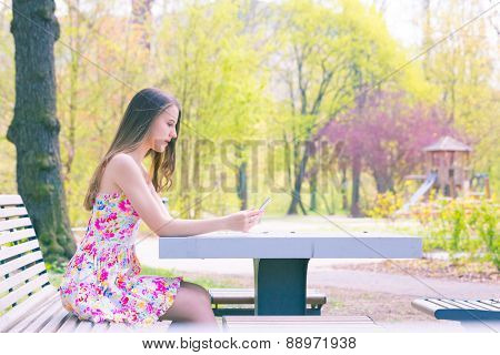 Young woman in short colorful dress sitting on a bench in summer city park and used a mobile phone or smartphone, look at phone, toned photo
