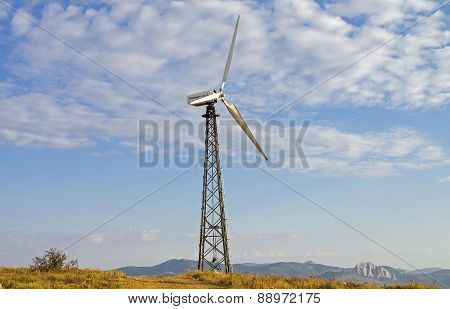 Mast With Wind Power Generator On The Background Of Sky.