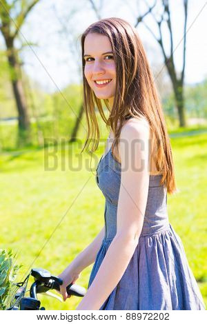 Young woman with long hair use bike for traveling in nature, look at camera and smile