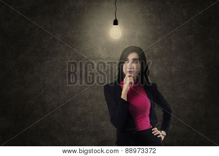 Busineswoman Thinking Under Light Bulb