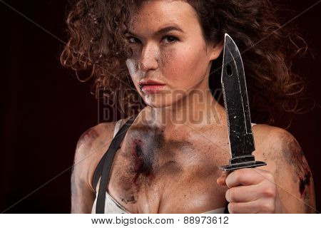 Young military woman posing with knife. Ready to fight. With dirty face, wound and blood.